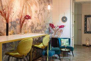 espacio para grupos, en primer plano hay una mesa alta blanca y dorada, con unas flores rojas . en el fundo hay 2 sillones azules con cojines verdes. en la pared hay un papel pintado efecto selva salvaje. la decoración general es moderna y elegante