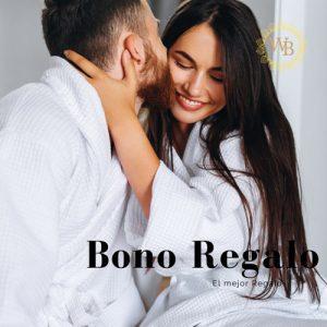 pareja en Albornoz en un spa. el hombre le esta dando un beso en la mejilla de la mujer. La mujer tiene una sonrisa