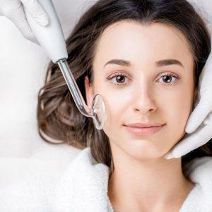 foto del rosotro de una mujer recibiendo un tratamiento facial antiacné de alta frecuencia